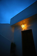 """SHOT 2/10/09 7:12:25 PM - Dusk settles in as a star shaped lighting fixture lights up a doorway in the Petit Hotel Hafa in Sayulita, Mexico. Located on Calle Jose-Mariscal in Sayulita Mexico, Petit Hotel d'Hafa is a quaint boutique hotel just steps away from the Sayulita plaza and less than a two minute stroll to the beach and surfing break. Sayulita is a small fishing village about 25 miles north of downtown Puerto Vallarta in the state of Nayarit, Mexico. Known for its consistent river mouth surf break, roving surfers """"discovered"""" Sayulita in the late 60's with the construction of Mexican Highway 200. Today, Sayulita is a prosperous growing village of approximately 4,000 residents. Hailed as a popular off-the-beaten-path travel destination, Sayulita offers a variety of activities such as horseback riding, hiking, jungle canopy tours, snorkeling and fishing. Still a mecca for beginner surfers of all ages, the quaint town attracts upscale tourists with its numerous art galleries and restaurants as well. Sayulita has a curious eclectic quality, frequented by native Cora and Huichol peoples, travelling craftsmen as well as international tourists. Sayulita is the crown jewel in the newly designated """"Riviera Nayarit"""", the coastal corridor from Litibu to San Blas. It's stunning natural beauty and easy access to Puerto Vallarta have made Sayulita real estate some of the most sought after in all of Mexico..(Photo by Marc Piscotty / © 2009)"""