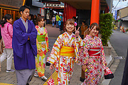 Young smiling Japanese girls in traditional kimono dresses. A Japanese man in traditional dress can be seen on the left. Photographed at the Fushimi Inari Taisha Shrine, Kyoto, Japan