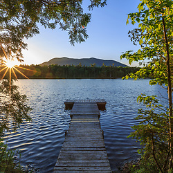 The sun sets behind Baker Mountain as seen from the dock on Little Lyford Pond in Maine's 100 Mile WIlderness near the Appalachian Mountain Club's Little Lyford Lodge.