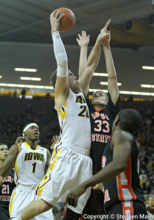 December 04 2010: Iowa Hawkeyes forward Andrew Brommer (20) puts up a shot over Idaho State Bengals center Deividas Busma (33) during the first half of their NCAA basketball game at Carver-Hawkeye Arena in Iowa City, Iowa on December 4, 2010. Iowa won 70-53.