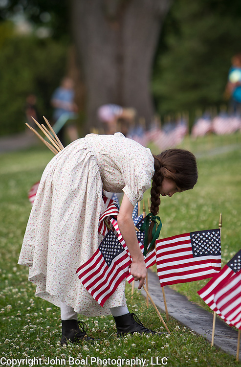 Erica Neemeyer, 11, plants flags at the Soldiers National Cemetery, during the Sesquicentennial Anniversary of the Battle of Gettysburg, Pennsylvania on Sunday, June 30, 2013. A pivotal moment in the Civil War, over 50,000 soldiers were killed, wounded or missing after 3 days of battle from July 1-3, 1863.  Later that year, President Abraham Lincoln returned to Gettysburg to deliver his now famous Gettysburg Address to dedicate the cemetery there for the Union soldiers who died in battle.  John Boal photography