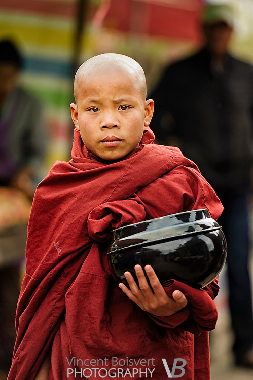 a young Buddhist monk collecting food in his alms bowl in the early morning, kalaw, myanmar