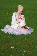 a woman in a period dress is sitting in the grass, reading a book