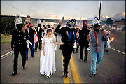 """Isabela Lucero, 10, La Malinche for this year's festival, leads the dance as the community processes down N.M. 337, the only road through town. """"The Malinche is very, very special. She is dressed in white, pure white. That (symbolizes) she is a virgin and she is getting ready to receive her communion,"""" said town elder Ernest Gutierrez."""