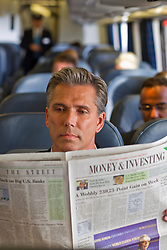man on a train reading a newspaper