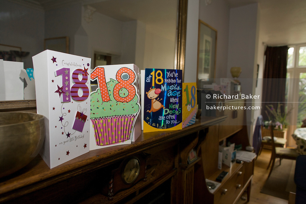 18th birthday cards mark the rite of passage, from childhood to adulthood, on a living room mantlepiece.