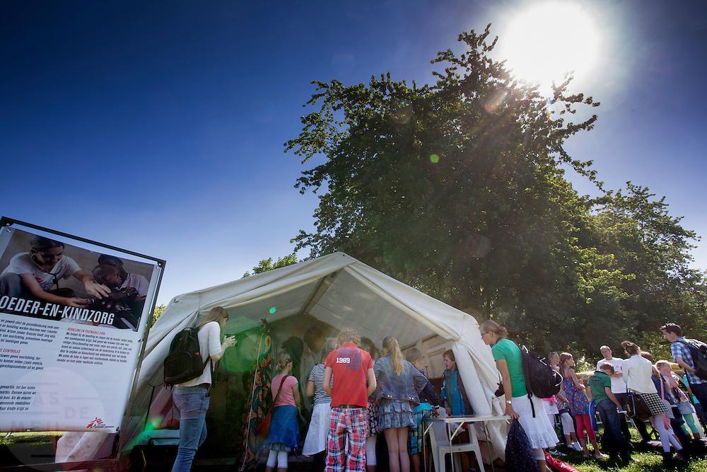 Basischolieren luisteren naar uitleg bij de moeder- en kinderzorg. In Utrecht heeft Artsen Zonder Grenzen een tentenkamp opgezet in het park Lepelenburg. Met het kamp wil de organisatie laten zien welk medische noodhulp het verricht in de noodhulpkampen in de wereld. Hulpverleners van AZG geven rondleidingen door  onder meer een (opblaasbaar) veldhospitaal, een voedingskliniek en een cholerakliniek.<br /> <br /> In Utrecht, MSF has set up a tent camp in the park Lepelenburg. In the camp, the organization wants to show what kind of emergency medical services they provide in the emergency camps in the world. MSF aid workers give tours including a (inflatable) field hospital, a nutrition clinic and a cholera clinic.