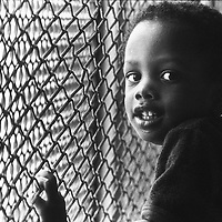 "A child resident of the Cabrini Green Housing Development in Chicago, Illinois stands at the fencing the covered the building's walkways. Photographed for the Gannett series, ""Equality, America's Unfinished Business."""