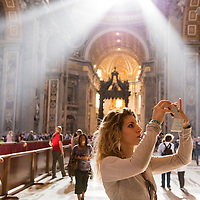 Italy, Vatican City, Attractive young woman photographs vast interior of Saint Peter's Basilica with her cellphone