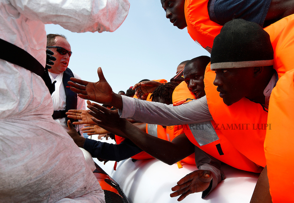 Migrants reach out to grab hold of Migrant Offshore Aid Station (MOAS) rescuers on a RHIB (Rigid-hulled inflatable boat) before  being taken to the MOAS ship MV Phoenix some 20 miles (32 kilometres) off the coast of Libya, August 3, 2015.  118 migrants were rescued from a rubber dinghy off Libya on Monday morning . The Phoenix, manned by personnel from international non-governmental organisations Medecins san Frontiere (MSF) and MOAS, is the first privately funded vessel to operate in the Mediterranean.<br /> REUTERS/Darrin Zammit Lupi <br /> MALTA OUT. NO COMMERCIAL OR EDITORIAL SALES IN MALTA