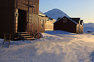Late evening sun shines on international science village of Ny-Alesund amid April snows on Spitsbergen island in Kongsfjorden; Svalbard, Norway.