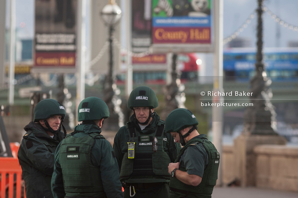Ambulance staff wearing body protection after four people were killed (including the attacker) and 20 injured during a terrorist attack on Westminster Bridge and outside the Houses of Parliament, on 22nd March 2017, in central London, England. Parliament was in session and all MPs and staff and visitors were in lock-down while outside, the public and traffic were kept away from the area of Westminster Bridge and parliament Square, the scenes of the attack. It is believed a lone man crashed his car into pedestrians then, armed with a knife tried to enter Parliament, stabbing and killing a police officer at parliament's main gates.