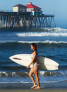 Woman Walking On Beach Holding Surf Board