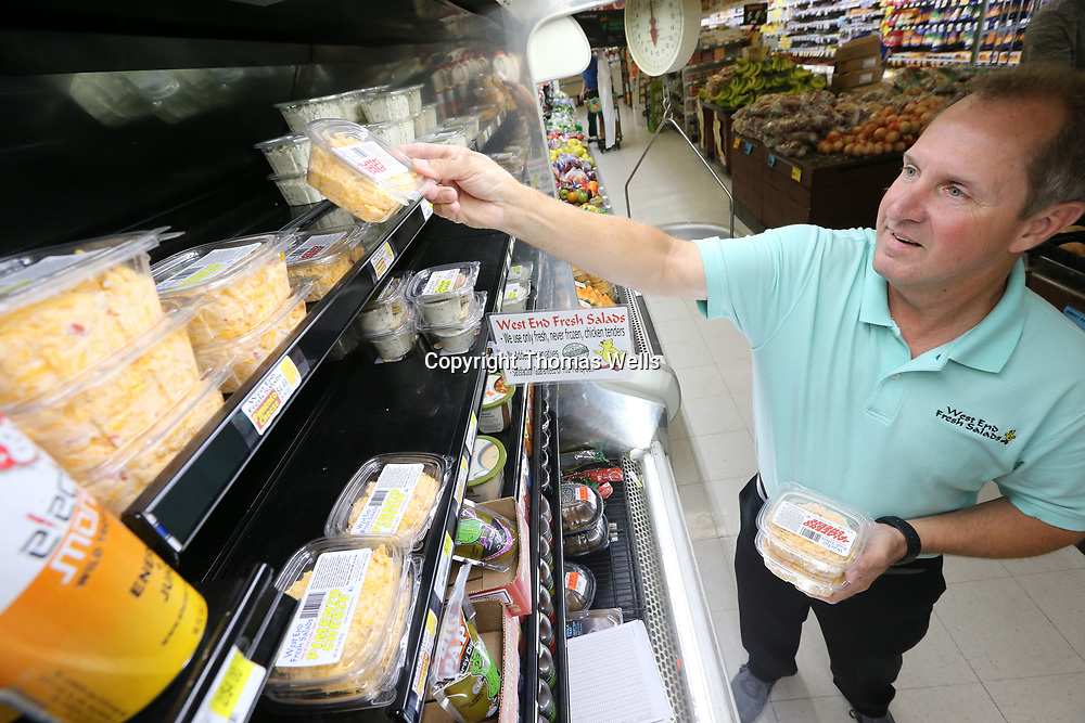Bruce Parker owner of West End Salad begins restocking the shelves at Todd's Big Start in Tupelo with his chicken and pimento cheese salads.