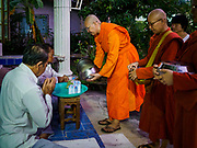 13 JANUARY 2019 - NAKHON PATHOM, THAILAND: A man gives food to female monks from Wat Songdhammakalyani on their alms rounds. The Sangha Supreme Council, Thailand's governing body of Buddhist monks, bans the ordination of female monks, but hundreds of Thai women have gone abroad, mostly to Sri Lanka and India, to be ordained. There are about 270 women monks in Thailand and about 250,000 male monks. There are 7 monks and 6 novices at Wat Songdhammakalyani in Nakhon Pathom. It was the first temple in Thailand to have female monks. The temple opened 60 years ago and has always been a temple of women monks. Women can be ordained as novices in Thailand, but to be ordained as a full monk would require the participation of 10 female monks and 10 male monks, and male monks in Thailand are barred from participating in women's ordination ceremonies.      PHOTO BY JACK KURTZ