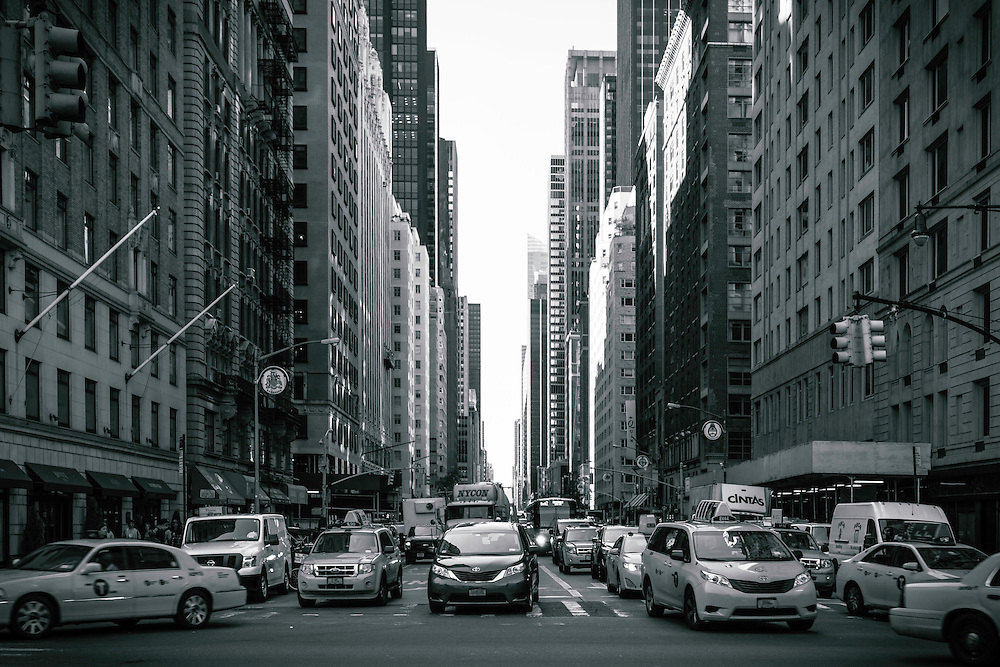Hustle and bustle as taxis and travelers fill the streets of Manhattan in New York City. Black and White.