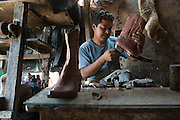 The boot cobbler, Julio Garcia Monroy, manufactures boots in his home shop.  He can produce a pair of boots in four hours of work.<br /> <br /> Photograph by Brian R. Page, brianpage.photoshelter.com