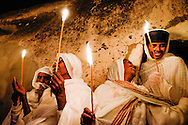 Ethiopian Christian woman hold candles, during holy saturday ceremony at Deir El Sultan in the Church of the Holy Sepulchre in  Jerusalem`s old city,  on  April 14, 2014.<br /> Photo by Oren Nahshon