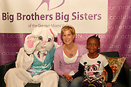Easter basket maker Janet Fernandes of Dayton (center) gets a picture with the Easter Bunny and a little sister at the Big Brothers Big Sisters of the Greater Miami Valley office in Moraine, Saturday, March 23, 2013.  Fernandes bought and stocked 200 Easter baskets this year.