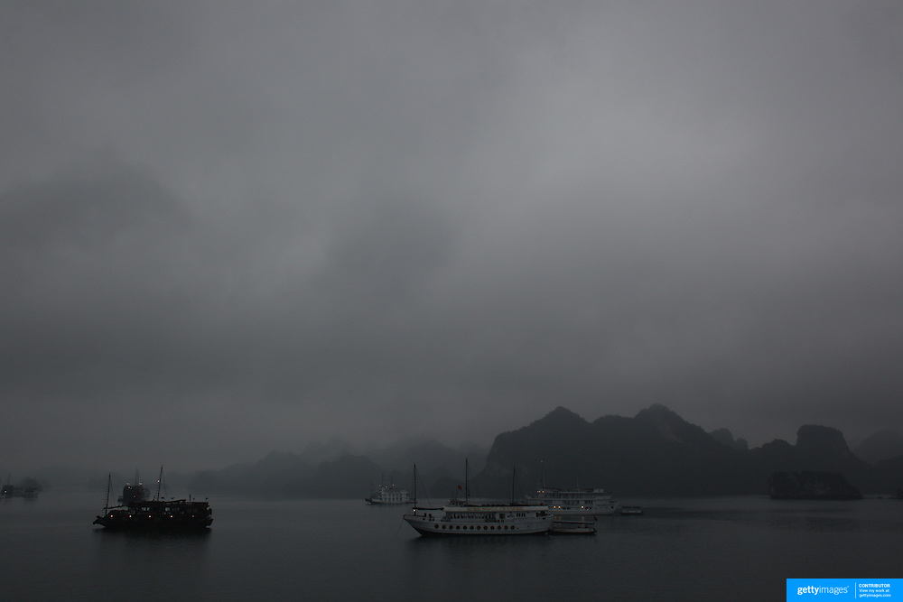 Early morning mist surrounds tourist Junks in Ha Long Bay, Vietnam. The bay consists of a dense cluster of 1,969 limestone monolithic islands. Ha Long Bay, is a UNESCO World Heritage Site, and a popular tourist destination. Ha Long, Bay, Vietnam. 11th March 2012. Photo Tim Clayton
