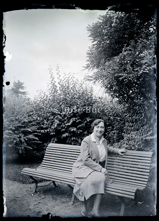 adult woman sitting on a garden bench France circa 1930s