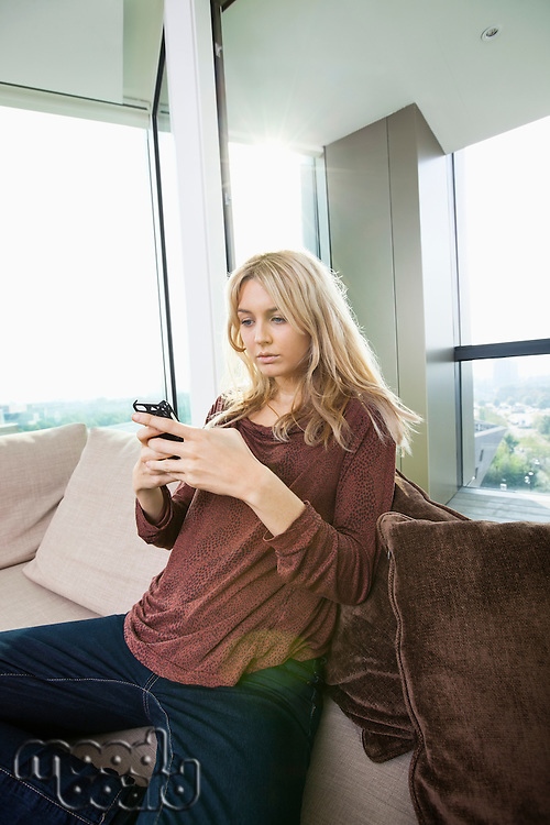 Side view of young woman text messaging at home