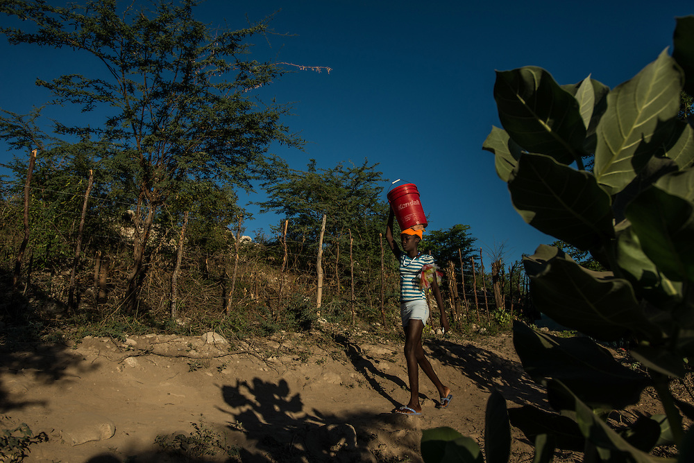 ANSE-A-PITRE, HAITI - NOVEMBER 23, 2015: A woman fetches river water shortly after dawn at Camp Cadeau 2. On this arid strip of borderland, the river brings life. Its languid waters cook the food, quench the thirst and bathe the bodies of thousands of Haitians who poured onto its banks this summer, fleeing threats of violence and deportation from their neighbors in the Dominican Republic.  These days, it is also brings death. Horrid sanitation has lead to a cholera outbreak in the camps, infecting and killing residents. PHOTO: Meridith Kohut for The New York Times