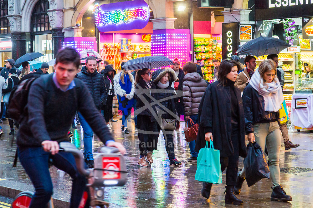 London, December 31 2017. The umbrellas come out as a downpour begins in London's west end ahead of the New Year's Eve fireworks at midnight. PICTURED: People make their way through the colourful reflections as the rain falls on Piccadilly . © SWNS