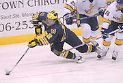 Michigan's Carl Hagelin (left) gets tripped up by LSSU's Chad Nehring (16, right) during the Wolverines Friday win over the LSSU Lakers at Taffy Abel Arena in Sault Ste. Marie.