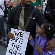 African American father with his daughter, just a few of the faces of the 99% protesters in Foley Square in lower Manhattan before they march to  Zuccotti Park.<br /> <br /> This movements is about income equality and social justice issues.