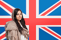 Portrait of beautiful young Muslim woman in traditional clothing standing against British flag