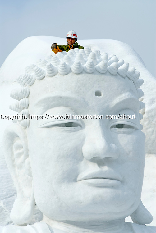 Worker carving large Buddha head from snow at annual Sapporo Snow Festival on Hokkaido Japan