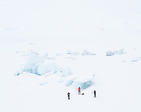 Photographers capturing snow covered ice bergs out on frozen Fjallsárlón Glacial Lagoon, Southeast Iceland.