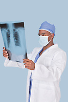 Male doctor analyzing x-ray report over light blue background