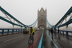 © Licensed to London News Pictures. 11/05/2016. LONDON, UK.  Early morning commuters cross Tower Bridge in London during foggy and wet weather this morning.  Photo credit: Vickie Flores/LNP