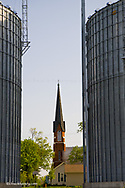 Powerful symbols of the Midwest as Historic St Marys Catholic Church is framed by grain bins in Utica Illinois