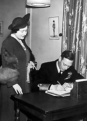 King George VI and Queen Elizabeth signing the visitors book at the recently opened Y.M.C.A. King George the Sixth Club in London after walking inside unannounced.