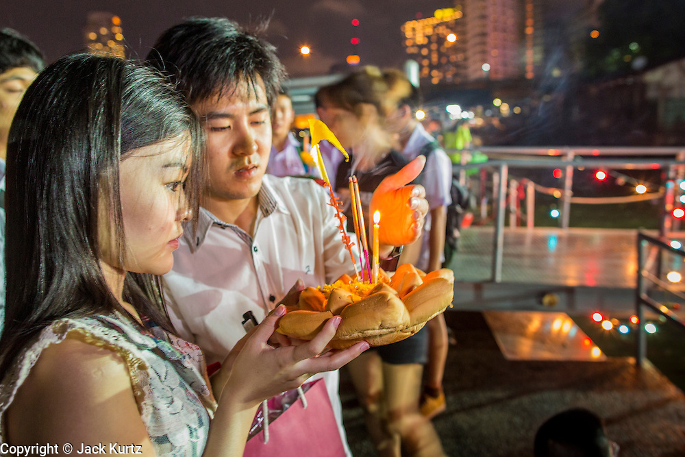 28 NOVEMBER 2012 - BANGKOK, THAILAND: A couple with a bread krathong pray before putting in the Chao Phraya River for Loy Krathong at Wat Yannawa in Bangkok. Loy Krathong takes place on the evening of the full moon of the 12th month in the traditional Thai lunar calendar. In the western calendar this usually falls in November. Loy means 'to float', while krathong refers to the usually lotus-shaped container which floats on the water. Traditional krathongs are made of the layers of the trunk of a banana tree or a spider lily plant. Now, many people use krathongs of baked bread which disintegrate in the water and feed the fish. A krathong is decorated with elaborately folded banana leaves, incense sticks, and a candle. A small coin is sometimes included as an offering to the river spirits. On the night of the full moon, Thais launch their krathong on a river, canal or a pond, making a wish as they do so.    PHOTO BY JACK KURTZ