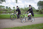 © Licensed to London News Pictures. 15/05/2014. Windsor, UK. Two women cycle along the banks of the River Thames. The second day of The Royal Windsor Horse Show, set in the grounds of Windsor Castle. Established in 1943. Photo credit : Stephen Simpson/LNP