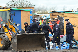 © Licensed to London News Pictures . 04/03/16 . A man being ushered by police with his belongings as workmen and French authorities continue to clear large parts of the migrant camp in Calais, known as the Jungle. Photo credit : Ian Homer/LNP