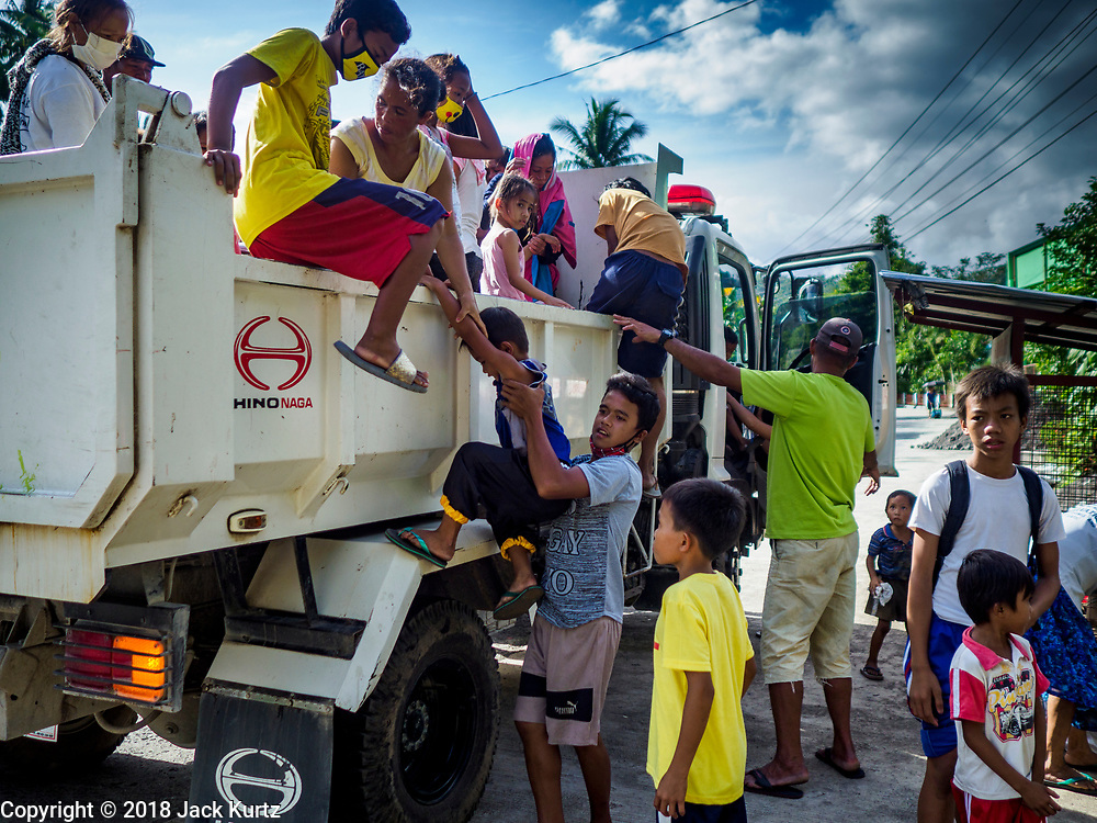 "22 JANUARY 2018 - CAMALIG, ALBAY, PHILIPPINES: People who live on the slopes of the Mayon volcano get out of a government truck after their arrival at an evacuation center. There were a series of eruptions on the Mayon volcano near Legazpi Monday. The eruptions started Sunday night and continued through the day. At about midday the volcano sent a plume of ash and smoke towering over Camalig, the largest municipality near the volcano. The Philippine Institute of Volcanology and Seismology (PHIVOLCS) extended the six kilometer danger zone to eight kilometers and raised the alert level from three to four. This is the first time the alert level has been at four since 2009. A level four alert means a ""Hazardous Eruption is Imminent"" and there is ""intense unrest"" in the volcano. The Mayon volcano is the most active volcano in the Philippines. Sunday and Monday's eruptions caused ash falls in several communities but there were no known injuries.    PHOTO BY JACK KURTZ"