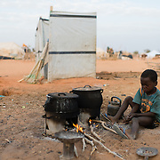 A child tends the fire as his family's breakfast of porridge warms at the Mbera camp for Malian refugees in Mauritania on 3 March 2013.