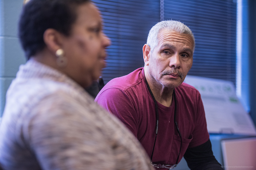 Gisela Nelson, executive director of New Legacy Reentry Corp,, and husband Paul Nelson, Sr., speak with Michael Jones at New Legacy. They have seven community members living in their building on Garvin Place. (Photo by Brian Bohannon)