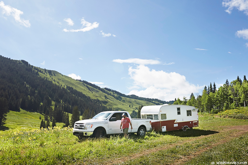 A truck and camper trailer setting up in a field of wildflowers near Crested Butte, Colordao.