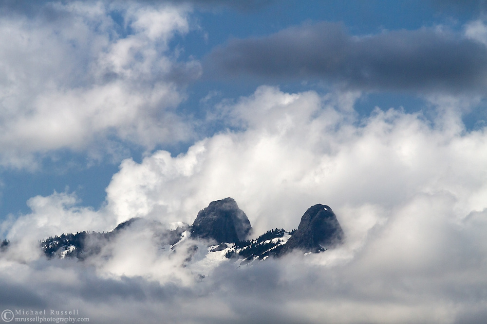 The Lions emerge from the clouds in British Columbia's Northshore Mountains.  Photographed from Capilano River Regional Park in North Vancouver, British Columbia, Canada