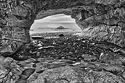 View of rocks along the Gulf of St. Lawrence at dusk as seen though the rock arch. Northern Peninsula. <br />The Arches Provincial Park<br />Newfoundland & Labrador<br />Canada<br />The Arches Provincial Park<br />Newfoundland & Labrador<br />Canada