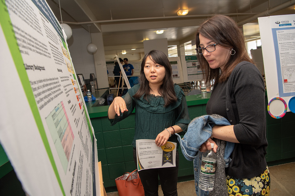 """Xinyue Ren receives the Library Student Assistant Award for her work titled, """"What social media can do when designing hybrid on- boarding experiences for Library studetn workers"""" from Janet Hulm, Interim Dean of University Libraries at the Student Expo. Photo by Ben Siegel"""