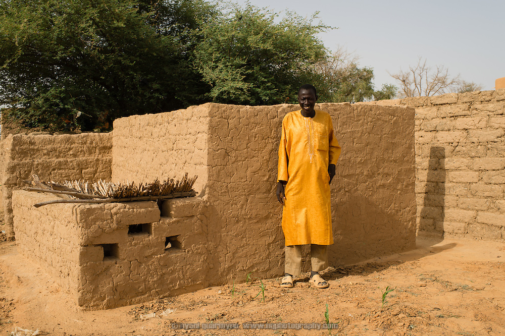 Namata Idi, 39, beside the low wall of a latrine he built in his family compound in the village of Gadirga in the Commune of Soukoukoutan in the Dosso Region of Niger on 23 July 2013. Under a WaterAid Community-Led Total Sanitation (CLTS) program, the cost of cement covers for such latrines is subsidized, reducing the cost to the owner from CFA 5000 to CFA 3000. Idi says he is peased that there is no more waste around the village which would allow flies to carry disease between excrement and food, and that waste can no longer be washed into their water sources.
