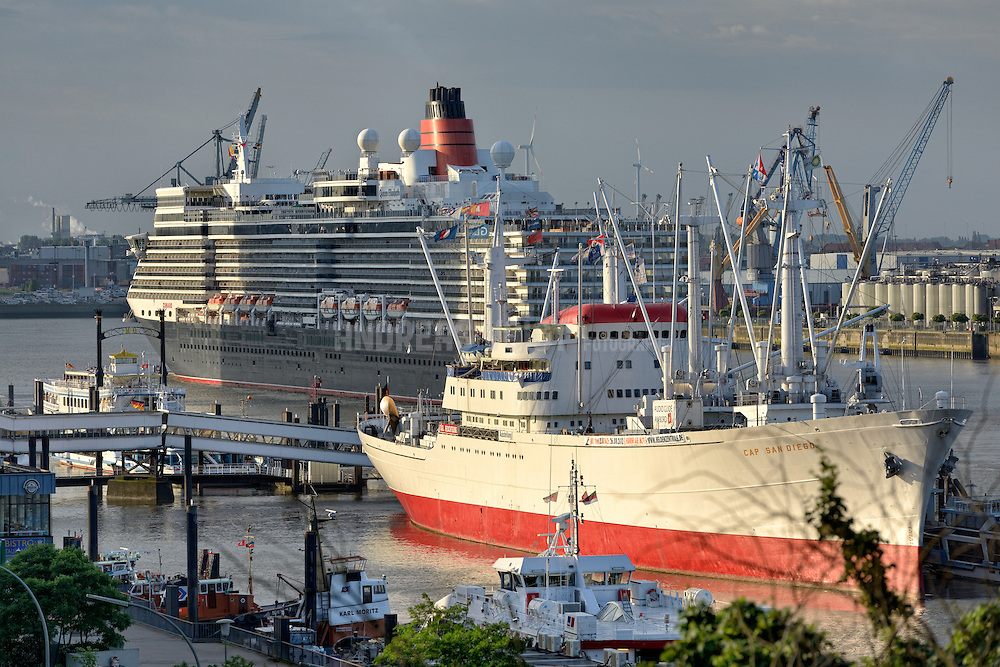 Die 'Queen Elisabeth' bei der Einfahrt in den Hafen Hamburg mit Blick auf die Landungsbrücken und auf das Museums-Frachtschiff 'Cap San Diego'