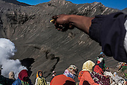 Villagers stand on the inner slope of Bromo crater in order to catch the offerings that thrown into by Tenggerese worshipers during Yadnya Kasada ritual, in Lumajang, East Java, Indonesia, August 15, 2011. Tenggerese believe their ancestors Princes Roro Anteng and Prince Joko Seger sacrificed their 25th child to the volcano after their wish to be given children were fulfilled by the gods. Later on, Tenggerese continue the ritual by delivering offerings such as vegetables, fruits, money, livestock and paddy to the crater of Bromo volcano.